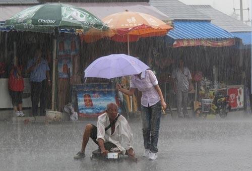 น้ำใจงาม! สาวจีนกางร่มบังสายฝนให้ชายชราขาพิการ